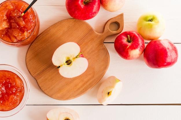 Варенье из яблок в стеклянной банке и половинка спелого яблока на доске в форме яблока. вид сверху. концепция здорового питания.