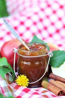 항아리에 사과 잼과 야외에서 신선한 빨간 사과