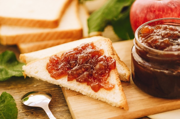 Apple jam on toast and in jar, fresh red apples on a cutting board on a wooden table.