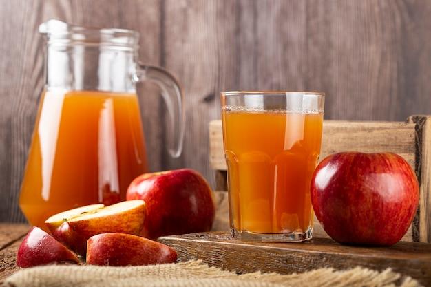 Яблочный сок и красные яблоки на столе.