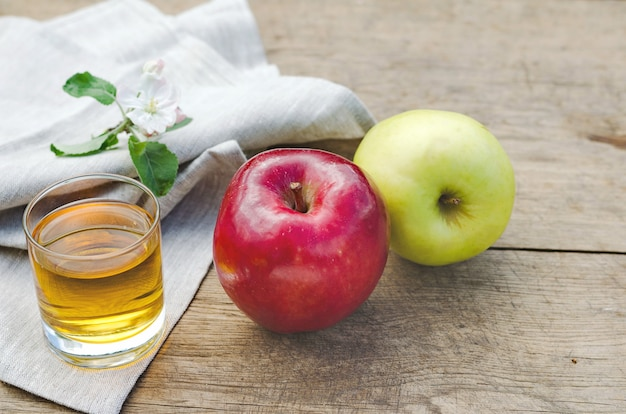 Apple juice and apples on a wooden table with a gray tablecloth
