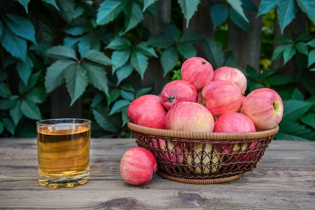 Apple juice in a glass and apples on a wooden table