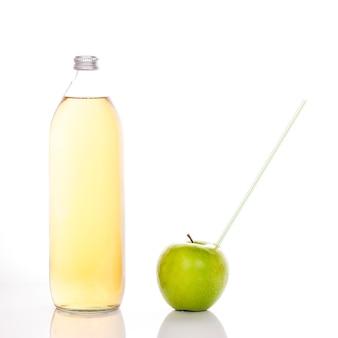 Succo di mela in una bottiglia di vetro e mela verde con paglia