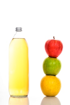 Apple juice in glass bottle and three ripe apples