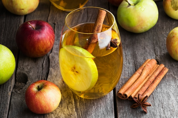 Apple juice in glass with cinnamon and anise