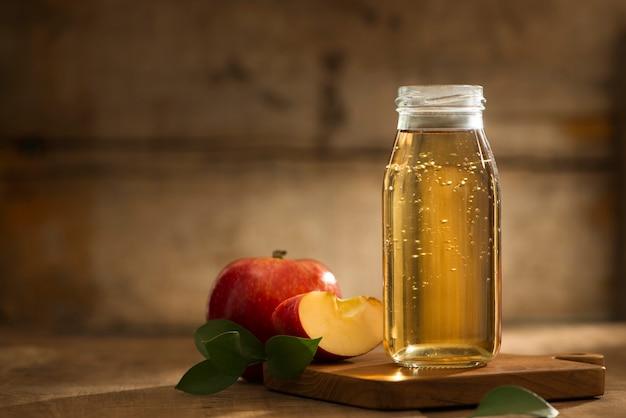 木製の背景に赤いリンゴをスライスした瓶とガラスのリンゴ ジュース