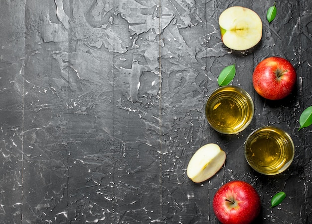 상자에 신선한 사과와 유리 항아리에 사과 주스. 어두운 소박한 배경.