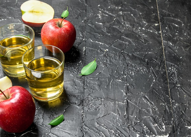 상자에 신선한 사과와 유리 항아리에 사과 주스. 어두운 소박한에.