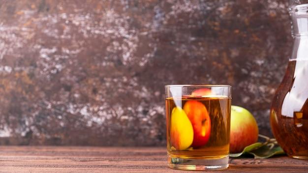 コピースペースのある木製のテーブルの上のガラスのリンゴジュース。フルーツドリンク、テキストスペース