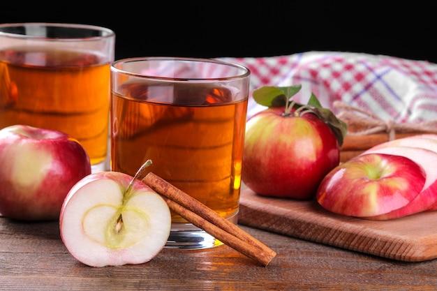 黒の背景に茶色の木製テーブルに新鮮な赤いリンゴとシナモンをたっぷりとガラスのリンゴジュース