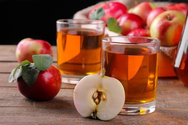 黒の背景に茶色の木製テーブルに新鮮な赤いリンゴがたくさん入ったガラスのリンゴジュース