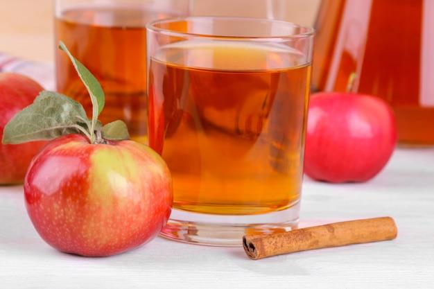 白い木製のテーブルの上に成熟した新鮮な赤いリンゴとシナモンとグラスのリンゴジュース