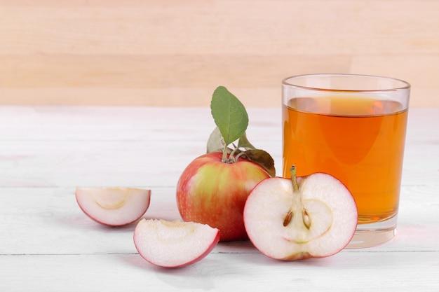 白い木製のテーブルの上に成熟した新鮮な赤いリンゴとガラスのリンゴジュース