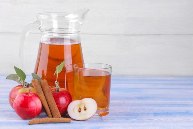 푸른 나무 테이블과 흰색 나무 배경에 있는 신선한 사과와 계피 스틱 옆에 있는 유리병과 사과 주스