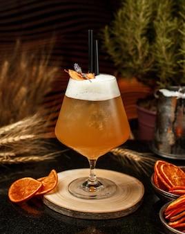 Яблочный сок в большой стакан со льдом, черная солома на деревянной доске
