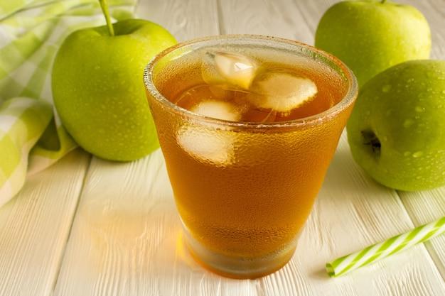 白い木製の背景のガラスのリンゴジュース