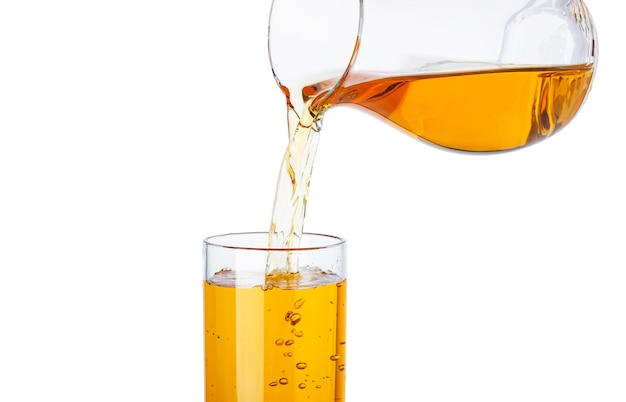 Apple juice pouring from pitcher into glass