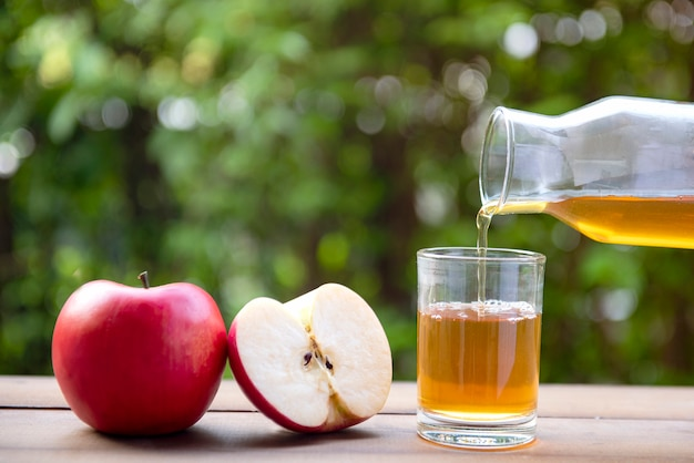 Apple juice pouring from red apples fruits