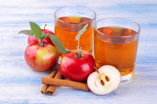 Яблочный сок с яблоками и палочками корицы на деревянном фоне