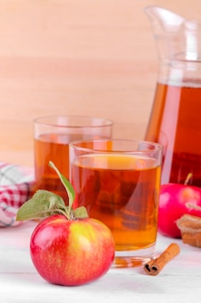 新鮮なリンゴとシナモン、自然な木製の背景にリンゴジュース