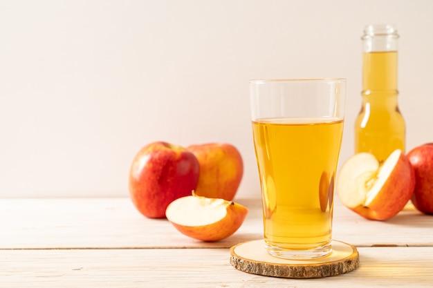 木の背景に赤いリンゴフルーツとリンゴジュース Premium写真