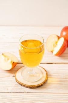 木の表面に赤いリンゴの果実とリンゴジュース