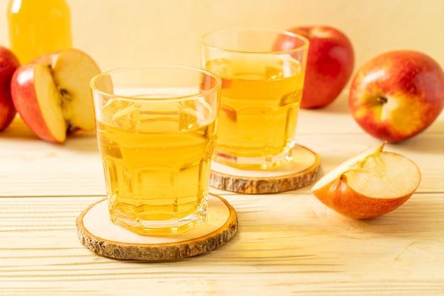 木製のテーブルに赤いリンゴの果実とリンゴジュース