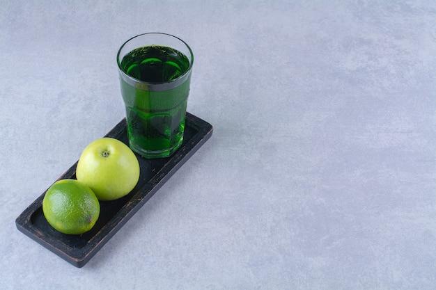 大理石のテーブルの上の木の板にリンゴ、レモン、リンゴジュース。