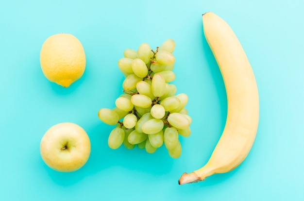 Apple lemon grapes and banana on turquoise surface