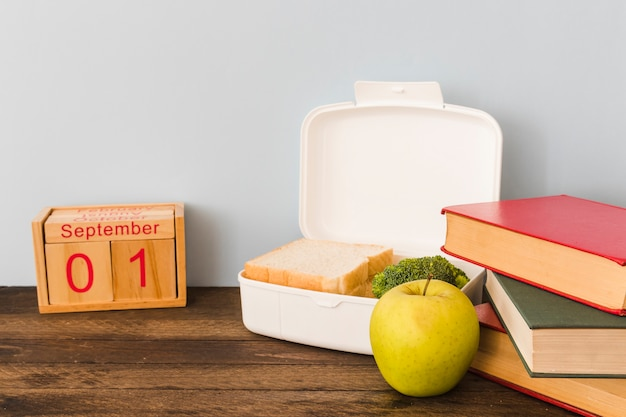 Apple and lunchbox between calendar and books