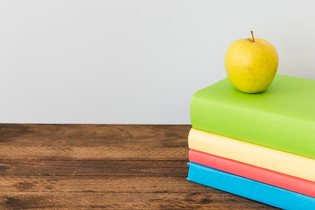 Apple lying on colorful books