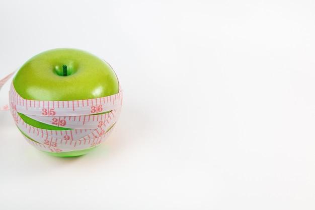 Apple & measuring tape on white background.
