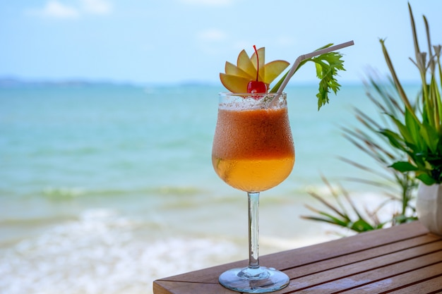 Apple mocktail with cherry in wine glass in tropical sea