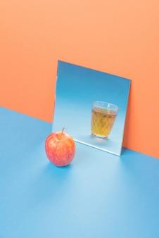 分離された青いテーブルの鏡でジュースとガラスの近くのリンゴ