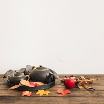 Apple near leaves and tea set