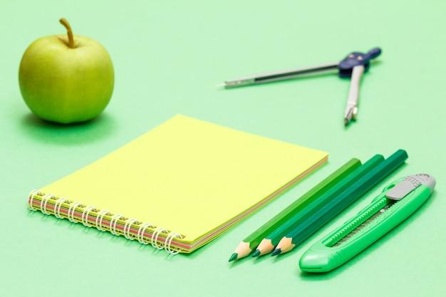 Apple, ноутбук, компас, цветные карандаши и нож для бумаги на зеленом фоне. снова в школу концепции. школьные принадлежности. малая глубина резкости.
