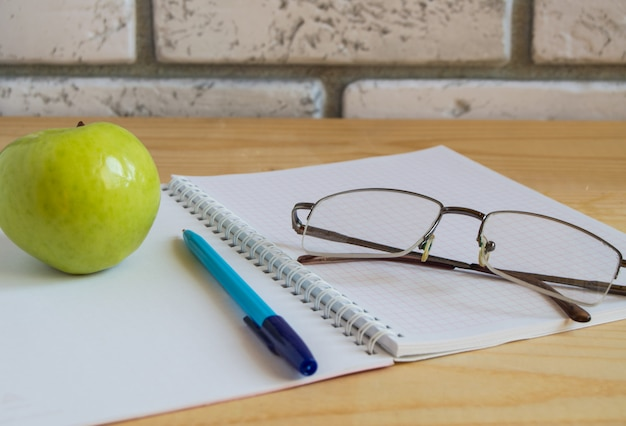 Apple, notebook, reading glasses and pen on wooden table.