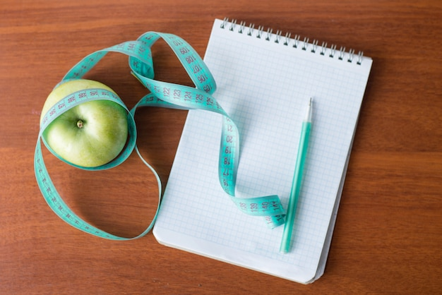 Apple and a notebook on a wooden background.diet concept. health
