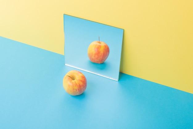 ミラーの近くの黄色に分離された青いテーブルの上のリンゴ