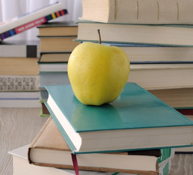 다른 책들 사이에 테이블에 책 더미에 애플