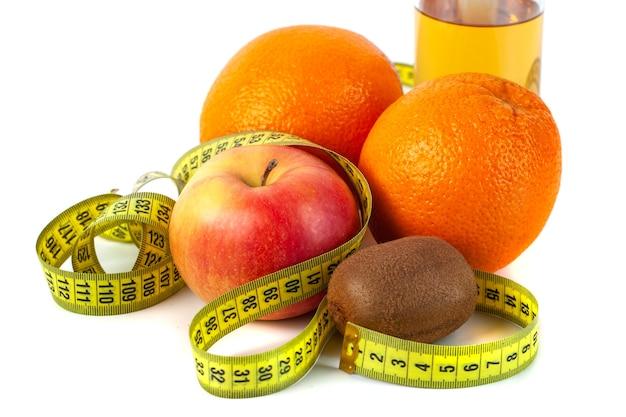 Apple, orange, kiwi with measure tape on white background, healthy diet.
