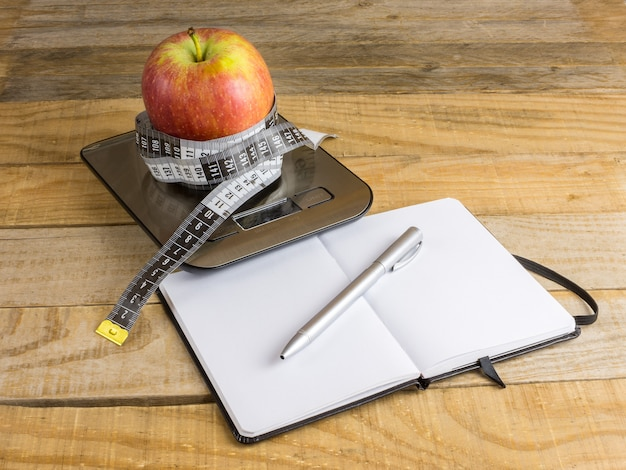 体重計、測定テープ、木製のテーブルの上のノートの上のリンゴ