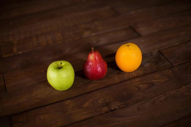 木製のテーブルにリンゴ、梨、オレンジ