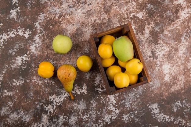 Mela, pera e pesche in una scatola di legno, vista dall'alto
