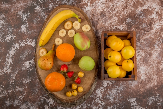 Apple, pear and peaches in a wooden box with berries aside, top view