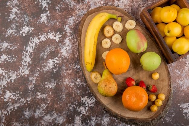 Mela, pera e pesche in una scatola di legno con bacche da parte