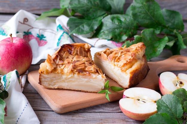 Яблочный пирог и красные яблоки на деревянном столе