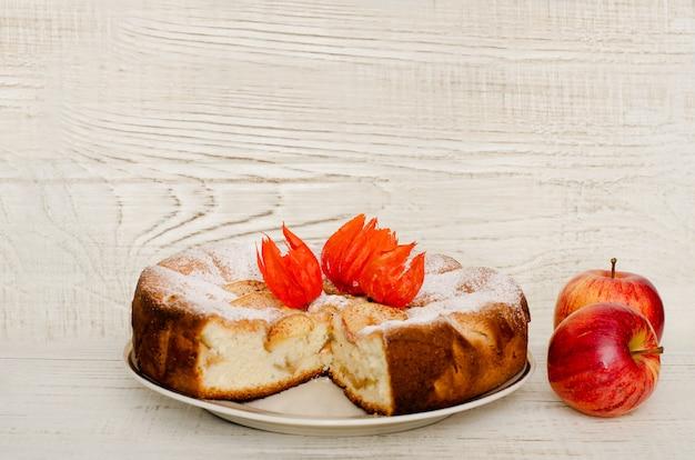 Яблочный пирог и спелые яблоки на светлой деревянной поверхности с местом для текста
