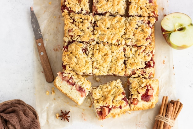 Apple pie bars with red berry jam, spices and crumble.