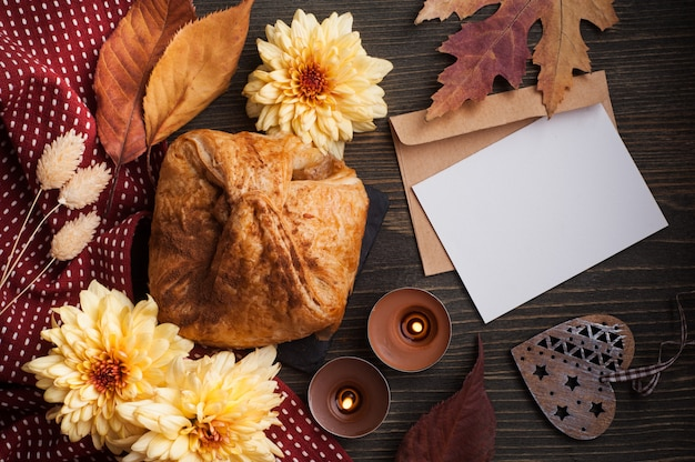 Apple pie on dark wooden background with leaves and candles